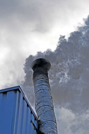 black smog from high industrial pipe with silver insolation on blue sky with white clouds, environment pollution diversity Banque d'images