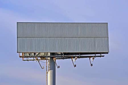 Huge empty wide billboard aka big board on pylon on blue sky, crisis advertising diversity
