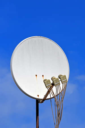 multi-feed satellite antenna with multiple feeds (converters) closeup on blue sky in sunny day, modern telecommunication diversity