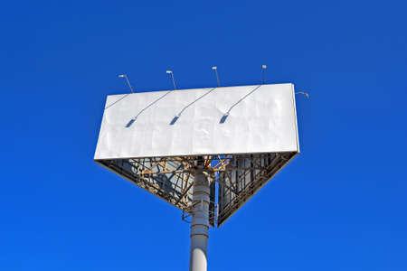 huge empty wide billboard aka big triangle board on pylon on blue sky, crisis advertising diversity Banque d'images