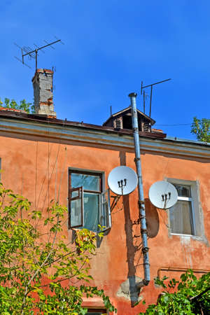 few television and multi-feed satellite antenna with multiple feeds (converters) on the vintage red building wall with open windows and high silver metal pipe, modern telecommunication diversity