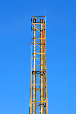 few high industrial silver pipe pylone on blue sky in sunny day, modern industry diversity