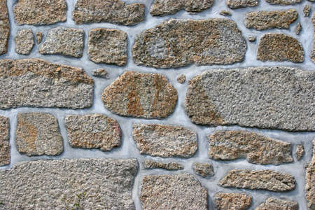 repaired: Ancient wall of granite stone repaired with fresh concrete Stock Photo