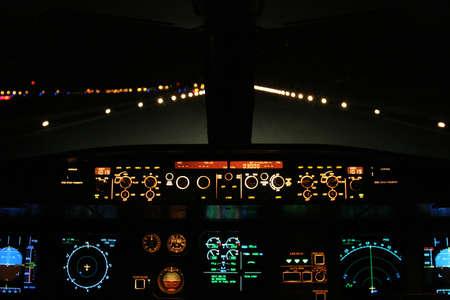 aircraft landing at night with runway ahead photo