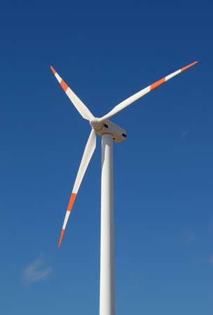 sustained: wind mill power generator against blue sky