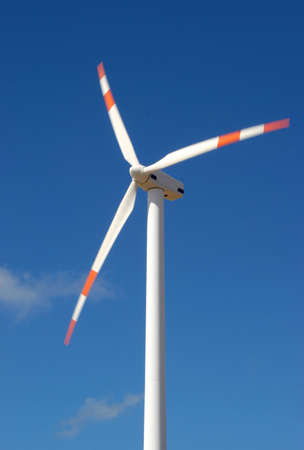 wind force: wind mill power generator against blue sky