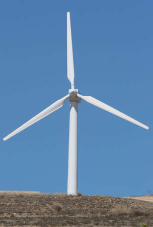 wind mill power generator with land against blue sky photo
