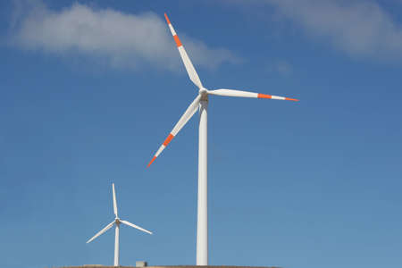 two wind mill power generators against blue sky photo