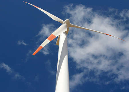 wind mill power generator against a cloudy blue sky photo