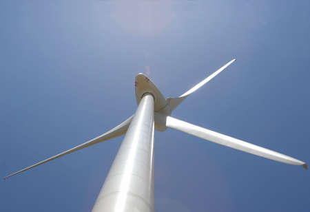 up perspective of wind mill power generator against blue sky with lens flare photo