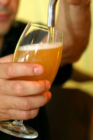 pouring fresh beer on a glass photo