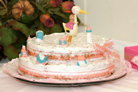 naming: baptism cake with small figurines and a stork on top