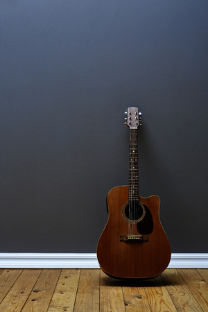 leaning against: Guitar leaning against wall in residential loft Stock Photo