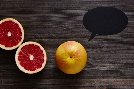 grapefruit with speech bubble and two halves