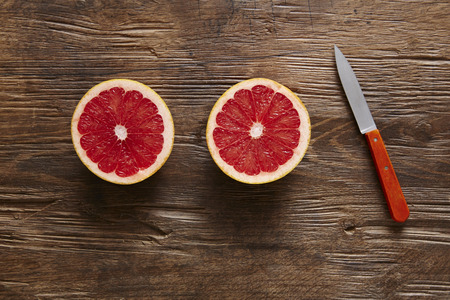 southsea: two halfs of sliced ??grapefruit with knife