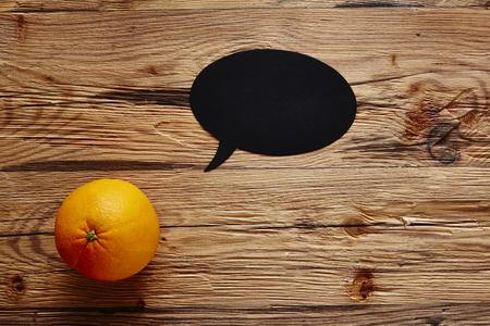 orange with speech bubble on wooden board Stock Photo