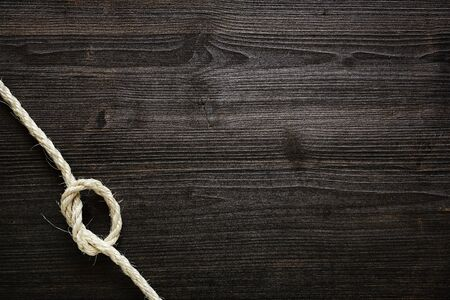 knotted rope on dark wood Stock Photo