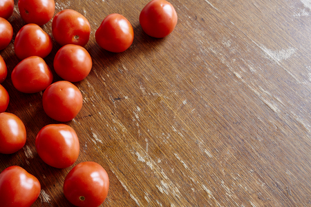 nightshade: fresh tomatoes framing wooden table
