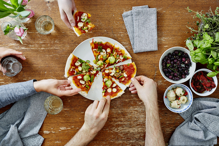 drei Menschen bei Dinnerparty organisch leckere Pizza teilen