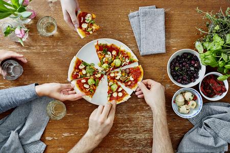 Drie mensen die biologische heerlijke pizza delen tijdens het dinerfeest Stockfoto - 70936938