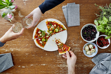 two people toasting with wine one person eating pizza
