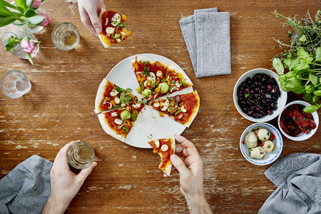 pizza base: two people sharing and eating pizza during dinner party
