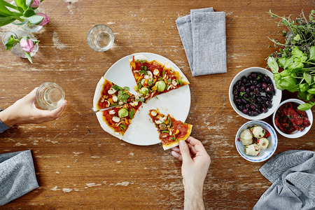 pizza base: eating and sharing organic pizza at dinner party Stock Photo