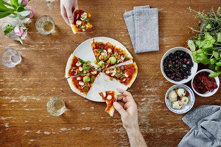 sharing and eating healthy organic pizza at dinner