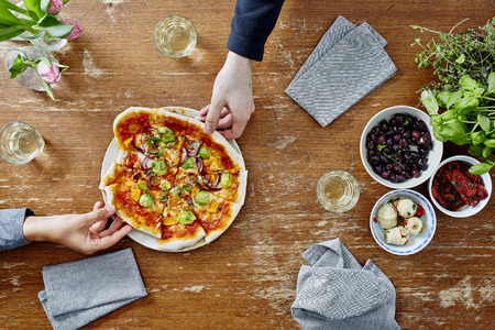 two people sharing freshly made vegetarian pizza Stock Photo
