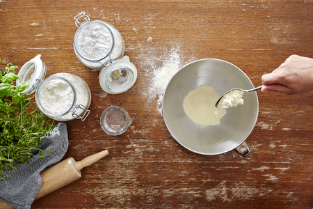 hand with spoon pouring flour into bowl baking scene on wooden table