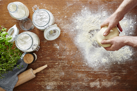 semolina pasta: hands kneading homemade dough wooden table and flour in kitchen