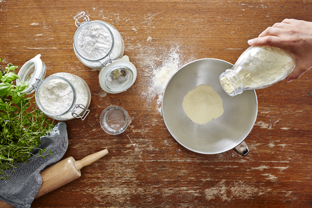 hand pouring flour into bowl homemade cooking