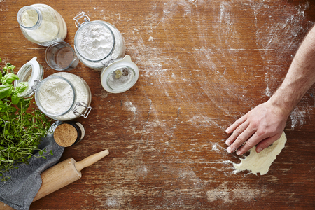 hand wiping flour on wooden workspace atmospheric kitchen scene