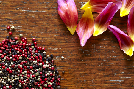 beautiful kitchen scene spicey pepper and colorful blossoms on dark wood