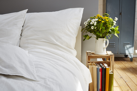 daybreak: white bed linen morning light fresh flowers industrial