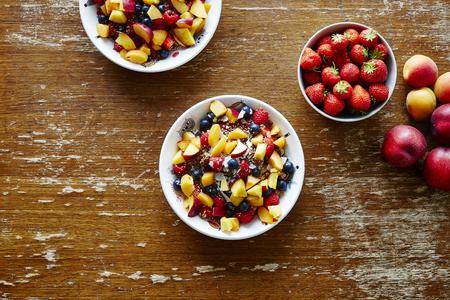 heathy: bowls of heathy organic muesli with fruits on wooden table helathy lifestyle