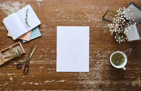 blank sheet of paper in creative workspace flowers and tea Stock Photo