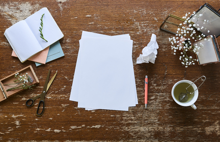 creative desk pictures flowers cup of tea and sheets of paper Stock Photo