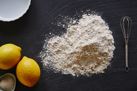 baking lemon pie foodist kitchen pile of flour on dark worktop