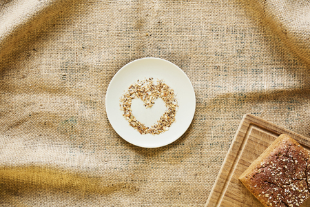 heart shaped bread crumbs on plate with bread Stock Photo