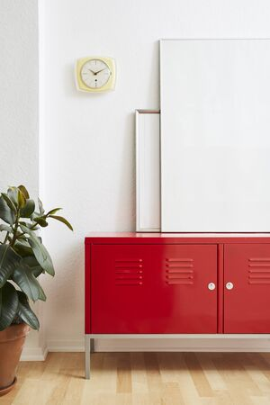 minimaist interior design large picture frames on red locker with clock and plant Stock Photo