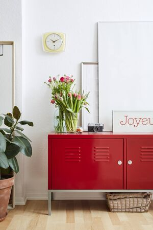 happy interior design flowers and large picture frames on red metal locker Stock Photo