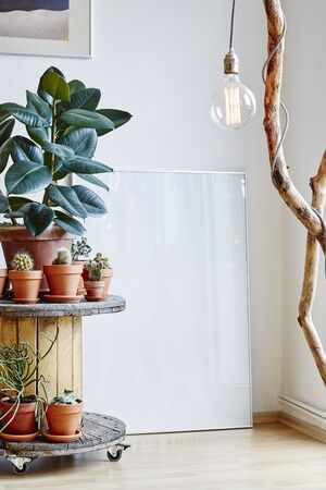 urban hygge interior design cable drum with plants and branch lamp in loft atmosphere