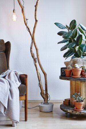 atmospheric interior design branch lamp cable drum table with plants and easychair