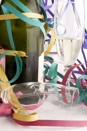 a bottle of champagne with two glasses an streamer