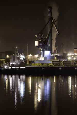 powe: Industrial crane in a port with nocturnal reflections Stock Photo