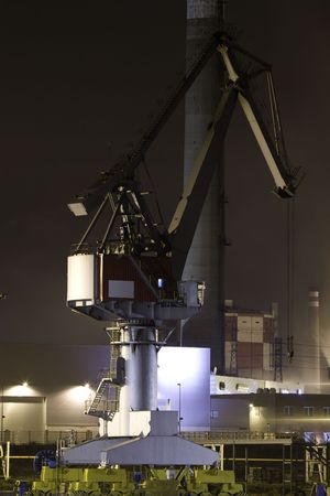 Industrial crane in a port with nocturnal reflections photo