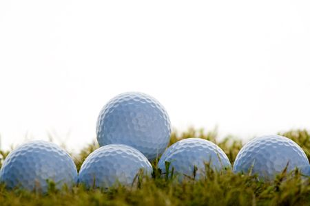 group of golf balls over grass in white background