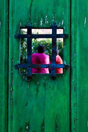 peephole: Antique peephole in a green wooden door