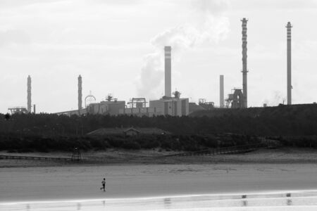 footing: man running by the beach in front of the chimneys of one trains in black and white